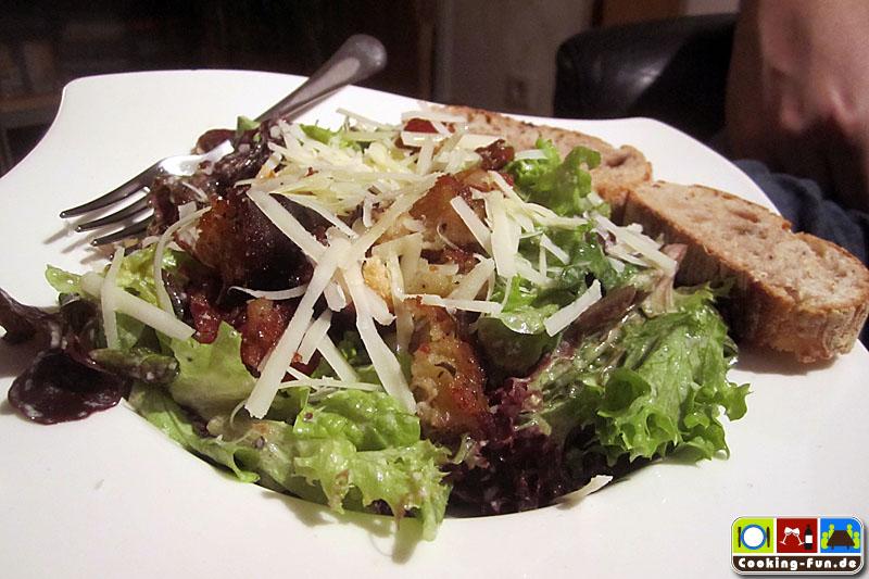 Salat mit Dressing, Fleisch und Croûtons anrichten, Parmesan drüberhobeln