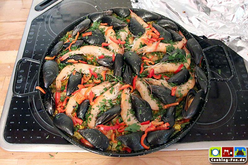 Paella noch mit Petersilie und letzten Paprikastreifen bestreuen und sofort servieren